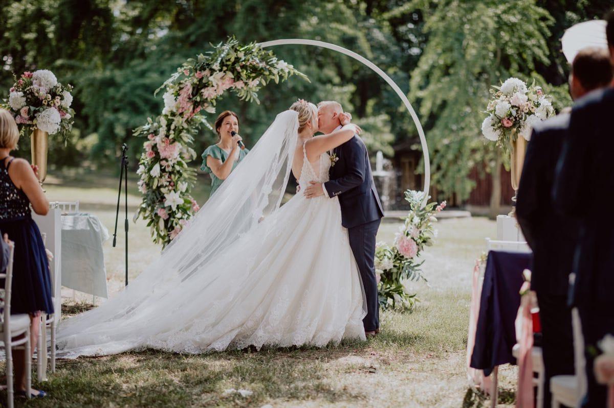 Hochzeitskuss Hochzeitsfotograf Dresden Schloss Proschwitz Hochzeitsbogen Blumen
